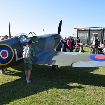 stationary Spitfire with crowd of people standing around it